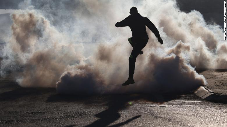 A protester jumps over smoke from burning tires during clashes with Israeli soldiers near the Hawara checkpoint, south of Nablus, on Friday.