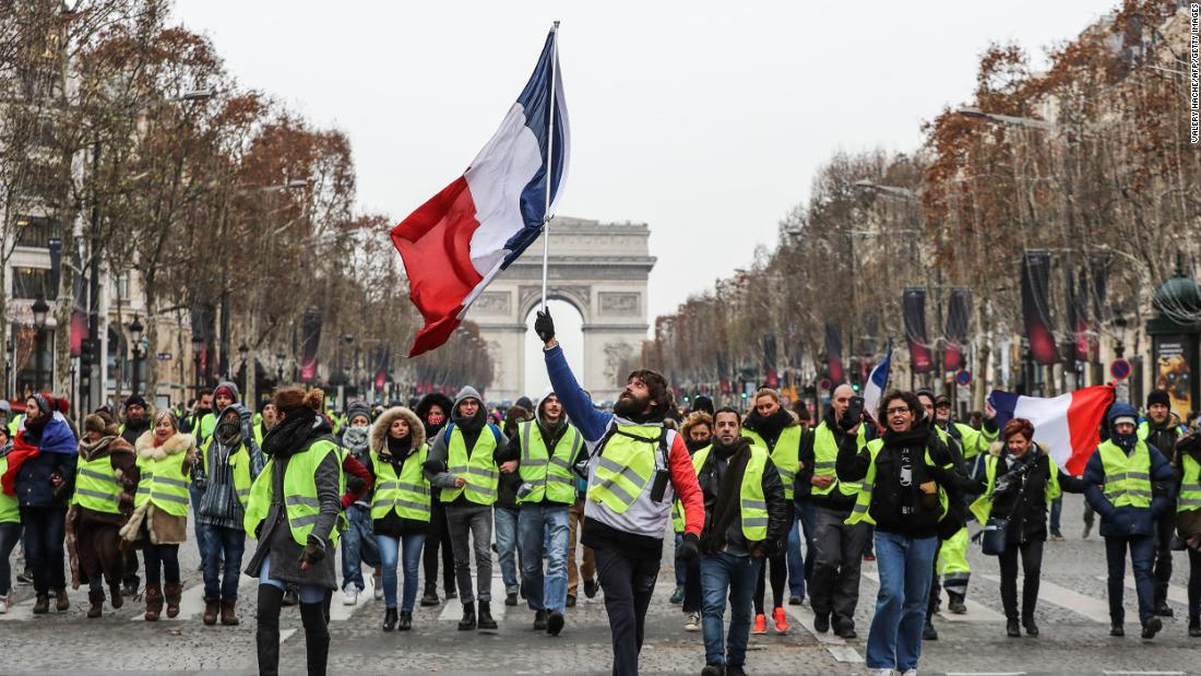 A protester waves the French national flag during a demonstration on the Champs-Élysées in Paris on December 15.