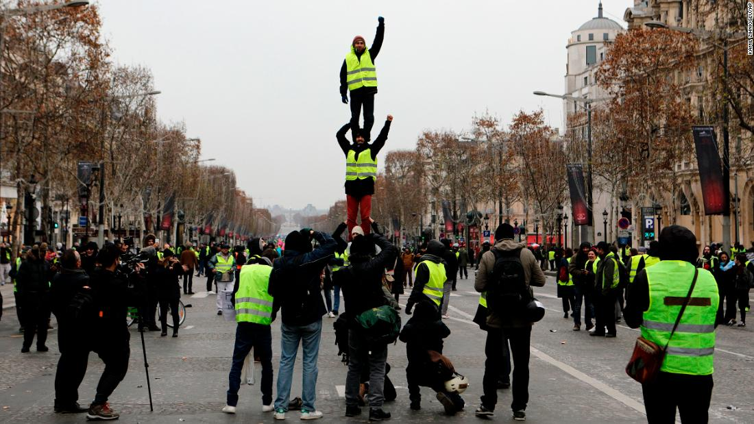 Demonstrators wearing yellow vests form a human tower December 15 on the Champs-Élysées in Paris.