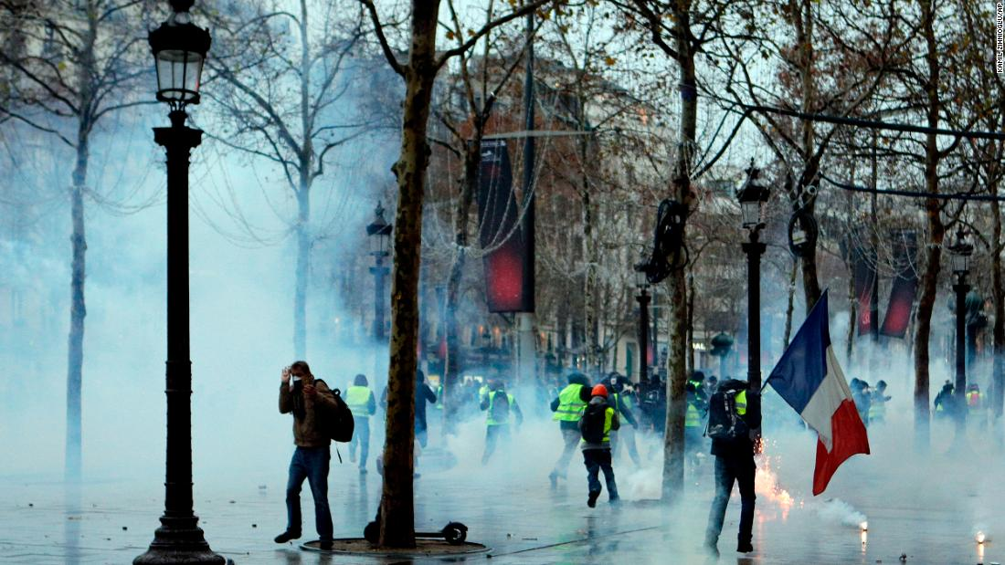 Demonstrators run through tear gas during scuffles with police December 15 on the Champs-Élysées in Paris.