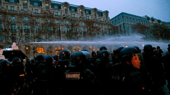 A police water cannon sprays demonstrators on December 15 in Paris.