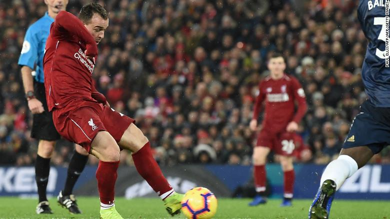 Xherdan Shaqiri shoots to score the third goal for Liverpool against arch-rival Manchester United.