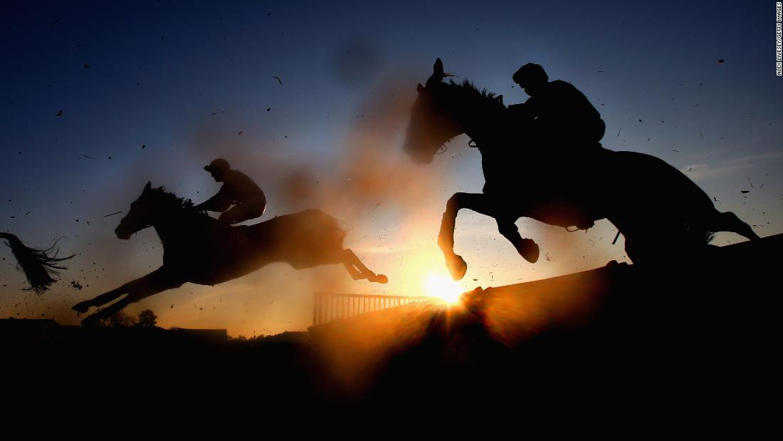 Horseback riders jump a fence during the Cliftons of Wrexham Novices' Hurdle Race in Bangor, Wales on Friday, December 14.