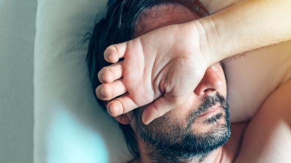 Morning depression and midlife crisis of a man in his 40s lying in bed in morning with symptoms like extreme sadness, frustration, anger and fatigue.  Chronic fatigue syndrome.; Shutterstock ID 680499979; Job: CNNie Design Website