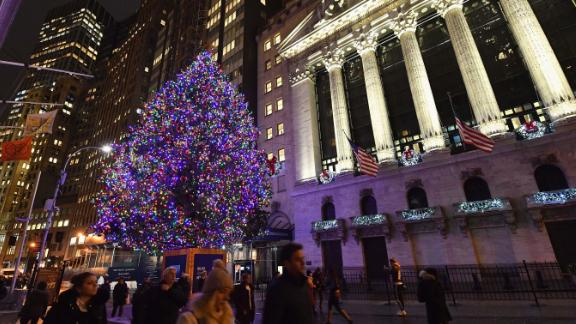People walk past a Christmas tree at the New York Stock Exchange on November 30, 2018 in New York City. - Wall Street finished a banner week on a positive note, borne higher by optimism about US-China trade talks while Microsoft overtook Apple in market value. Major US indices all finished the session solidly higher to cap a strong week. The S