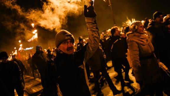 """BUDAPEST, HUNGARY - 2018/12/16: A protester seen holding a burning flare during the protest against the new labour law approved by the right wing conservative government lead by Viktor Orban. The Hungarian government has passed a set of controversial laws on judicial and labour topics, The new labour law, known as """"slave law"""" allows employers to ask their workers to take on up to 400 hours"""