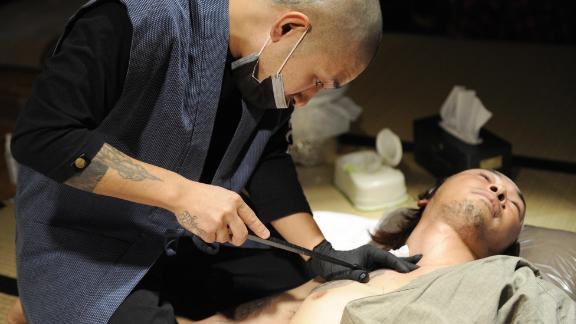 Japanese tattoo artist Horimyo (L) tattoos on the shoulder of calligrapher Hayato Suzuki prior to their collaboration event in Tokyo on February 25, 2009. Japanese tattooist demonstrated and exhibited his black and gray masterpieces for his Japanese traditional tattoo arts.   AFP PHOTO / Yoshikazu TSUNO (Photo credit should read YOSHIKAZU TSUNO/AFP/Getty Images)