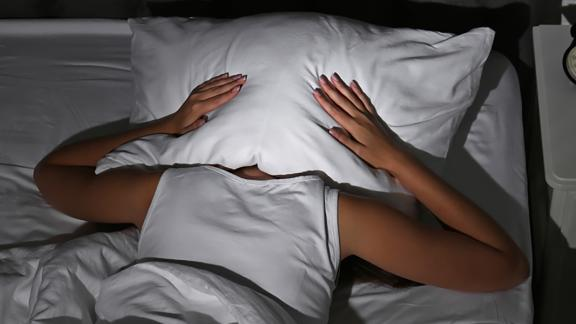 Young woman covering head with pillow in bed at home. Sleep disorder; Shutterstock ID 1163906941; Job: CNNie Design Website