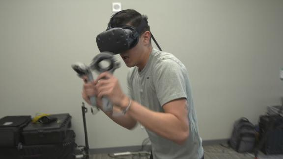 San Francisco State Kinesiology graduate student spars with virtual opponent as he tries out VR boxing game.