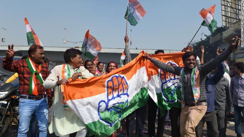 Сторонники партии Индийский конгресс держат флаг партии Конгресса во время празднования в Ахмедабаде 11 декабря 2018 года.