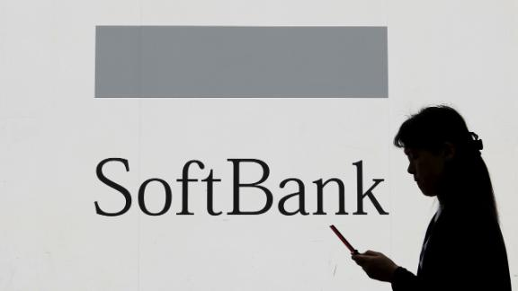 FILE PHOTO - A woman using a mobile phone walks past the logo of SoftBank Corp in Tokyo May 11, 2015. REUTERS/Toru Hanai/File Photo