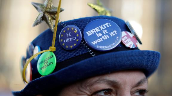 """A badge reading """"Brexit: Is it worth it?"""" is picture on the hoat of an anti-brexit activist as they protest outside the Houses of Parliament in central London on December 17, 2018, ahead of a statement by Britain"""
