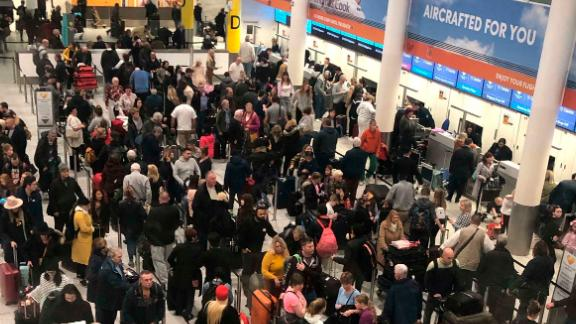 Lines of passengers wait at the check-in desks at Gatwick Airport.