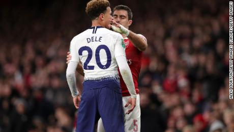 Deli Alli looks towards the fans after being hit by a water bottle.