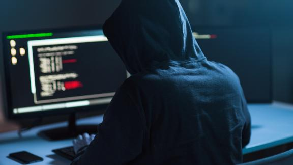 cybercrime, hacking and technology concept - male hacker in dark room writing code or using computer virus program for cyber attack; Shutterstock ID 1083511010; Job: -