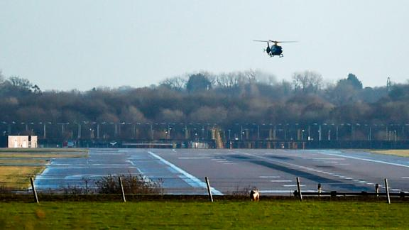 A police helicopter flies over the runway at Gatwick airport.