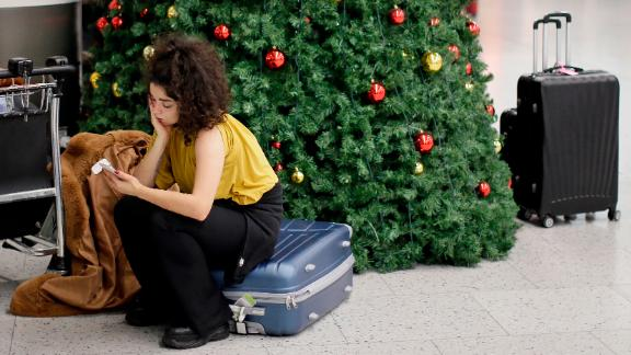 A woman waits in the departures area at Gatwick airport, near London, as the airport remains closed with incoming flights delayed or diverted to other airports, after drones were spotted over the airfield last night and this morning, Thursday, Dec. 20, 2018. London's Gatwick Airport remained shut during the busy holiday period Thursday while police and airport officials investigate reports that drones were flying in the area of the airfield. (AP Photo/Tim Ireland)