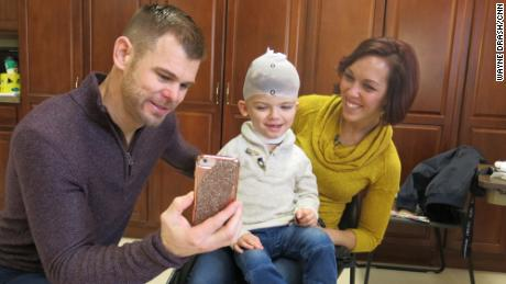 Christian and Nicole McDonald show Jadon photos on a phone while he gets measured for a new protective helmet.