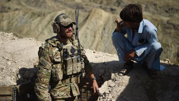 """In this photo taken on July 7, 2018, A US Army soldier from NATO and an Afghan Local Police (ALP) look on in a checkpoint during a patrol against Islamic State militants at the Deh Bala district in the eastern province of Nangarhar Province. - A US soldier was killed and two others wounded in an """"apparent insider attack"""" in southern Afghanistan on July 8, NATO said, the first such killing in nearly a year. (Photo by WAKIL KOHSAR / AFP)        (Photo credit should read WAKIL KOHSAR/AFP/Getty Images)"""