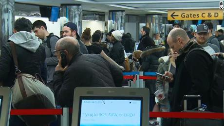 Travelers wait in line Friday at New York's LaGuardia Airport as a storm was expected to bring delays.