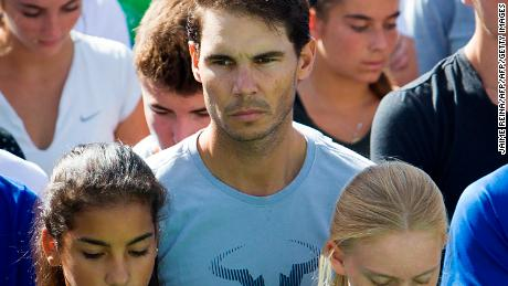 "Spanish tennis player Rafa Nadal (c) observes a minute of silence on October 11, 2018 with students and workers of the ""Rafa Nadal Academy"" in Manacor to honour the victims of the flash flood that affected the Spanish Balearic island of Majorca. - Hundreds of rescue workers searched desperately today for a five-year-old boy and two Germans still missing on Spain's holiday island of Majorca after flash floods tore through streets and swept away cars, killing 10 people. (Photo by JAIME REINA / AFP)        (Photo credit should read JAIME REINA/AFP/Getty Images)"