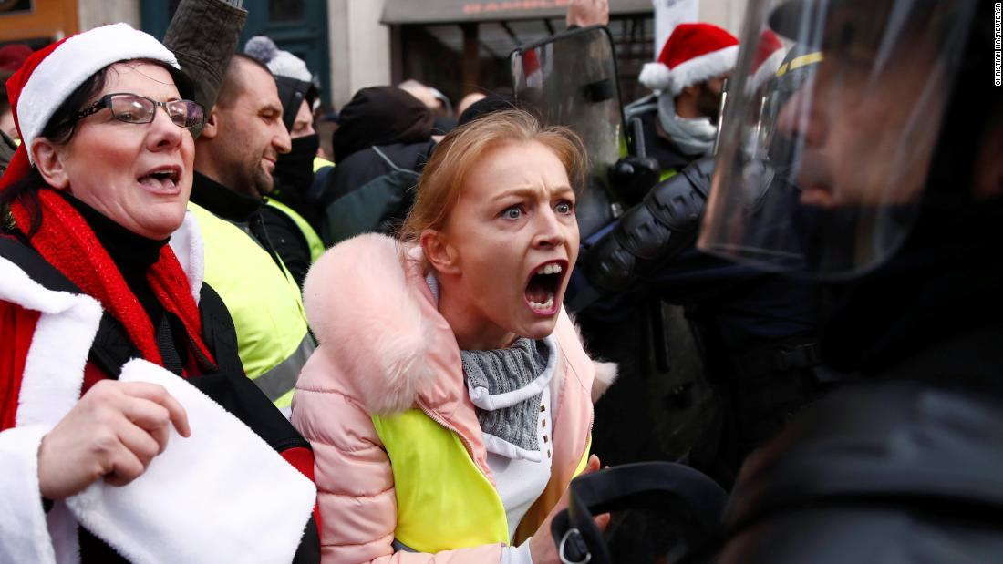 "Protesters confront police during a ""yellow vest"" demonstration Saturday, December 22, in central Paris."