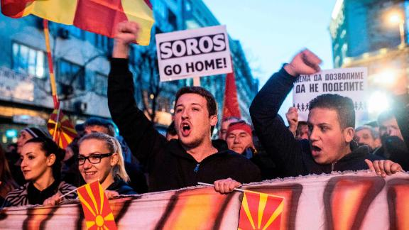 "People wave flags and chant slogans while a man carries a protest sign reading ""SOROS Go Home"" during a demonstration against a deal between Social Democrats and the Albanian Democratic Union for Integration, for a law making Albanian the second official language, on March 15, 2017 in Skopje. The Macedonian president, who has accused neighbouring Albania of trying to influence political developments across the border, referred to minority ethnic Albanian parties"