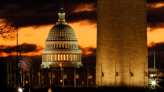 The U.S. Capitol dome is seen past the base of the Washington Monument just before sunrise in Washington, Saturday, December 22, 2018.