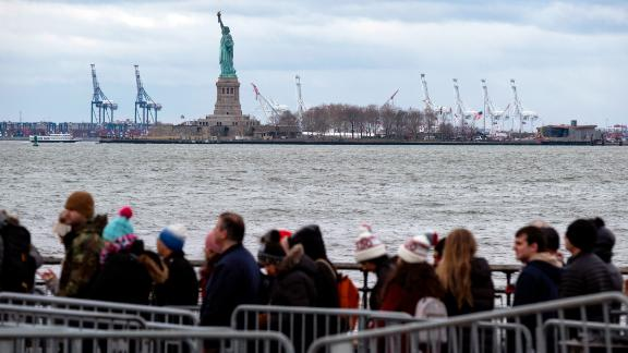 People line up to board a ferry to visit the Statue of Liberty on December 22. The national landmark remained open after New York Gov. Andrew Cuomo made funding available for it.