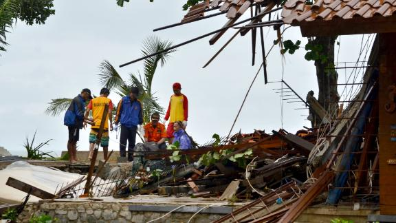 Officials look through the wreckage of damaged buildings in Carita, Indonesia.
