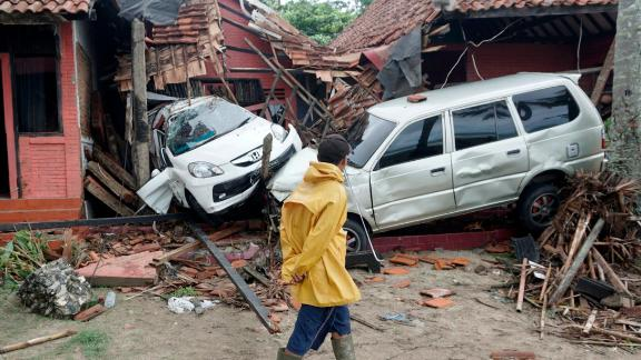 A villager walks past vehicles damaged by a tsunami in Carita, Indonesia.