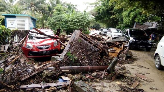 A damaged vehicle is seen amid wreckage from buildings along Indonesia