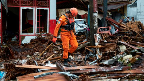 A rescue worker walks through the rubble from houses destroyed by a tsunami on December 23, 2018 in Carita, Indonesia.