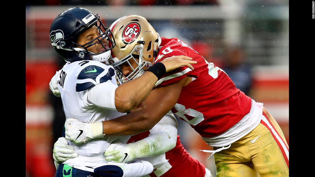 Seattle Seahawks quarterback Russell Wilson is hit by San Francisco 49ers linebackers Fred Warner and Elijah Lee during the second half of their football game in Santa Clara, California on Sunday, December 16.