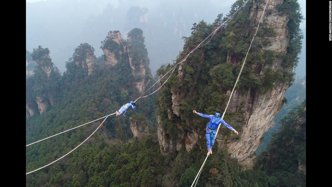 "Contestants dressed as characters from the movie ""Avatar"" take part in a tightrope walking contest on December 23 in Zhangjiajie, Hunan province, China."