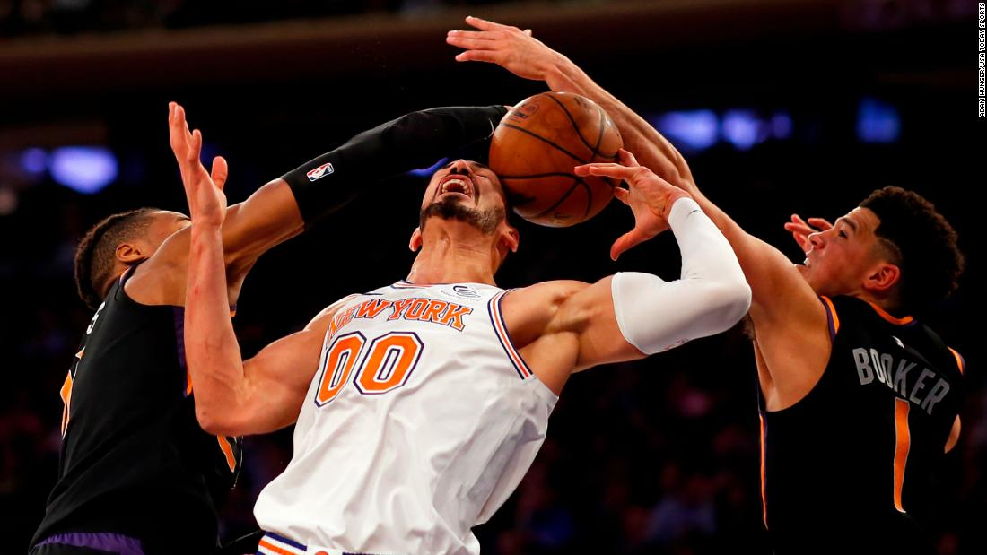New York Knicks center Enes Kanter is hit with the ball as he battles for a rebound between Phoenix Suns guards Devin Booker and Jamal Crawford  during the second half of their game at Madison Square Garden in New York City on December 17.