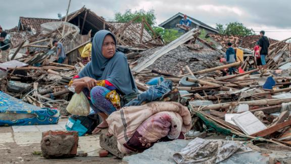 A survivor sits on debris as she salvages items from her destroyed house in Sumur, Indonesia.