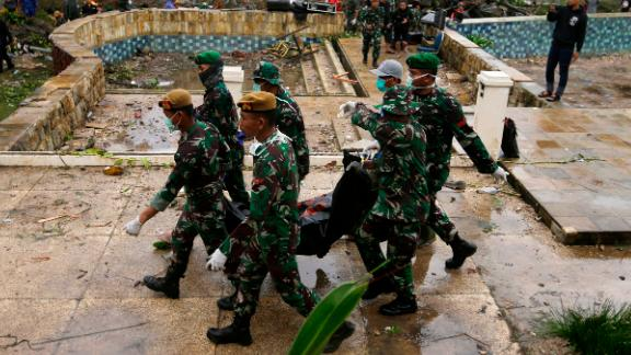 In this Monday, Dec. 24, 2018, photo, Indonesian soldiers carry the bodies of tsunami victims at a beach resort in Tanjung Lesung Indonesia. The tsunami that hit the coasts of Indonesian islands along the Sunda Strait was not big but it was destructive. The waves smashed onto beaches in the darkness Saturday night without warning, ripping houses and hotels from their foundations in seconds and sweeping terrified concertgoers into the sea. (AP Photo/Achmad Ibrahim)