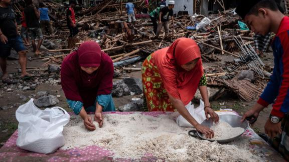 Women collect rice from their destroyed houses in Carita.