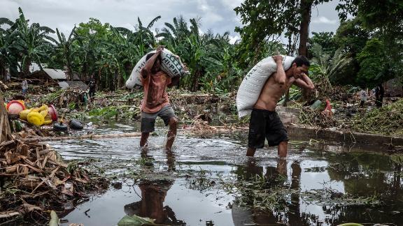 Villagers walk through debris in Carita, Banten province, Indonesia, on Monday following the tsunami.