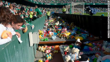 Real Betis fans throw stuffed animals to be collected and given to children in need.