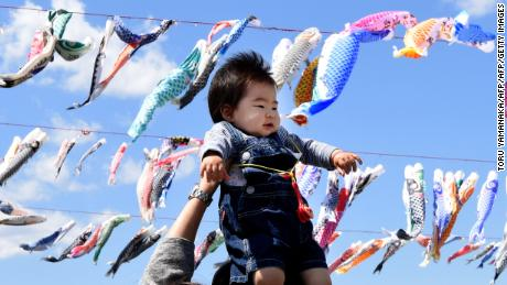 A father holds up his baby under carp streamers fluttering in a riverside park in Sagamihara, suburban Tokyo, on April 29, 2016 ahead of May 5 Children's Day in Japan.