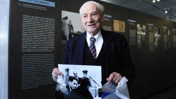 "Bach holds a photo as he tours the 2011 exhibit ""Facing Justice -- Adolf Eichmann on Trial"" in Berlin."