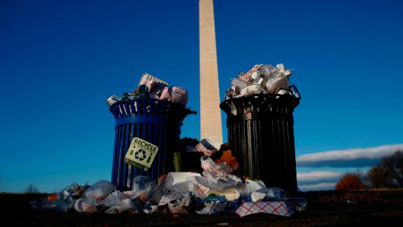 A public trash can spills over on Washington