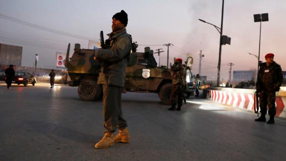 Afghan security forces stand guard at the site of the attack in Kabul.