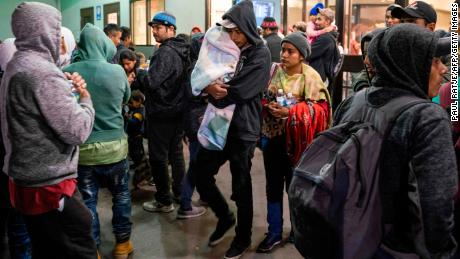Asylum seekers stand at a bus stop after they were dropped off by ICE at the Greyhound bus station in downtown El Paso, Texas, late on December 23, 2018.