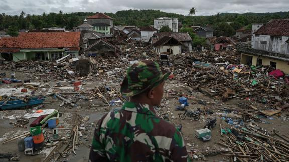 An Indonesian soldier looks at damaged houses and debris in Sumur, Indonesia, on Tuesday, December 25.