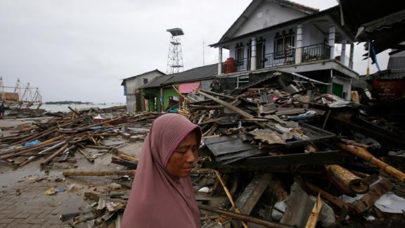 A tsunami survivor walks around Sumur on Tuesday.