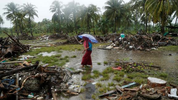 A woman holding an umbrella walks in the rain among debris after the tsunami in Sumur on Wednesday, December 26.