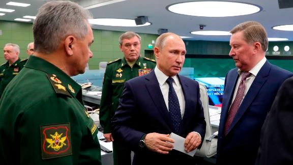 Russian Defense Minister Sergei Shoigu, left, Russian President Vladimir Putin, center, Chief of General Staff of Russia Valery Gerasimov, background center, and special representative on questions of ecology and transport, Sergei Ivanov, right, talk to each other as they come to oversee the test launch of the Avangard hypersonic glide vehicle from the Defense Ministry